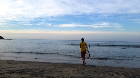 Kristen heading out at the main beach in Sayulita for a sunset session